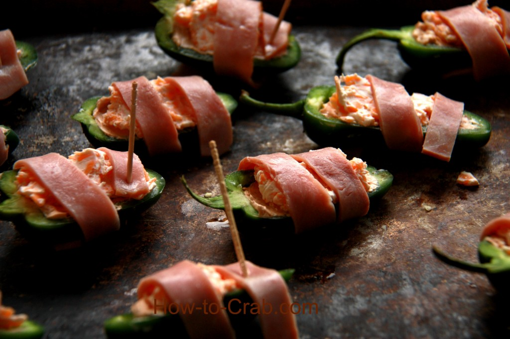 Bacon wrapped, cream cheese and crab filled jalapeno peppers.